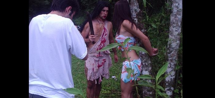 Goti Guerra, o terrível canibal armado de facão, aproxima-se da indefesa Edna Costa, enquanto Felipe M. Guerra filma tudo sem ajudar a moça!